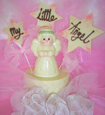 white chocolate angel on singe white chocolate tier, decorated with coloured chocolate and pink ribbon
