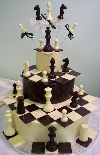 a picture of milk and white chocolate chess pieces on three chocolate tiers