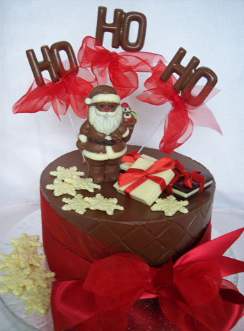 a picture of milk chocolate santa on singe milk chocolate tier, decorated with white chocolate and pink ribbon