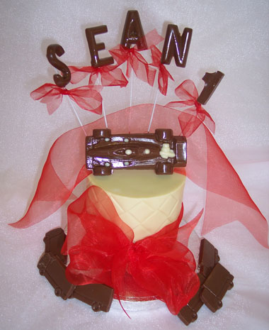 chocolate race car theme on single chocolate tier, decorated with ribbon