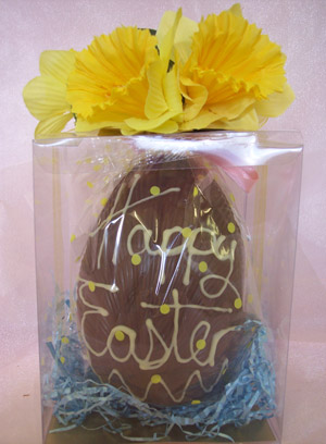 a picture of a Milk chocolate Easter egg nesting in a transparent box, decorated with white chocolate and yellow flowers.
