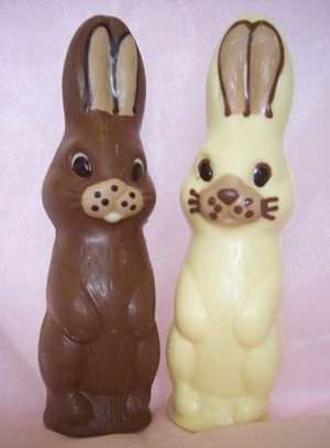A picture of two bunny rabbits. One milk, and one white chocolate. Each decorated with white, milk and dark chocolate.