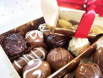 Hand-made chocolate truffles, gift wrapped in a gold box tied with ribbon