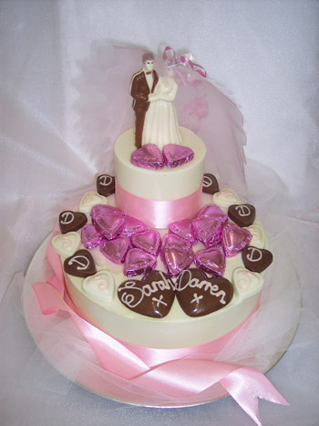 a picture of a chocolate bride and groom decorated with initialed love hearts on a chocolate tier