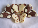 a picture of four small chocolate butterflies, decorated with milk and white chocolate