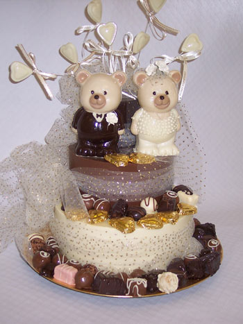 a picture of chocolate wedding teddies decorated with love hearts, truffles and ribbon, on a chocolate tier
