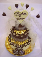 chocolate wedding tier decorated with personalized love hearts, truffles and ribbon