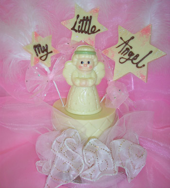 a picture of a white chocolate angel on a tier, decorated with coloured chocolate. Large chocolate snowflakes message reads 'My Little Angel'