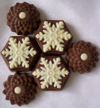 a picture of six chocolate snowflates, decorated with white and milk chocolate.